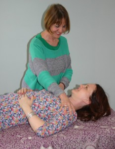 Teacher leans over student reclining on table.