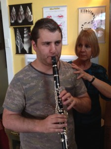 The teacher places her hand on a clarinetist's shoulder as he plays.